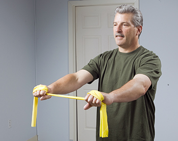 Man using resistance band to strengthen his shoulders and arms